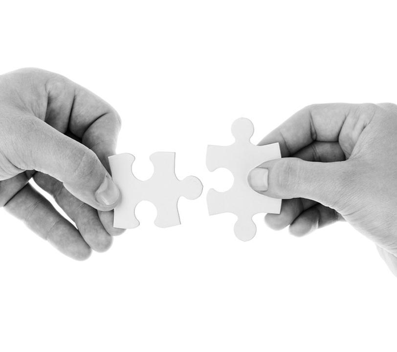Due mani che compongono un puzzle
